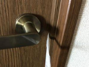 写真:ドアノブが壊れたときの脱出方法。ひもを持ちあげ、ラッチを押し上げる